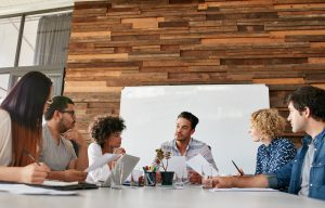 Group of business people having meeting in a board room in an office. Creative team sitting at the table discussing new strategy of their company.